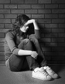 stock photo of depressed teen  - Teenage girl sitting against brick wall in depressed state