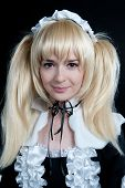 stock photo of lolita  - Portrait of young girl in anime lolita suit on black background - JPG