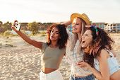 Three joyful girls friends in summer clothes taking a selfie at the beach poster