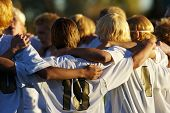 stock photo of huddle  - High school soccer team huddle showing teamwork and unity - JPG