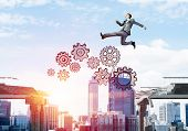 Businessman Jumping Over Gap With Gear Mechanism In Concrete Bridge As Symbol Of Overcoming Challeng poster