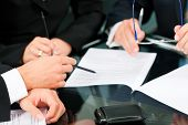Business - meeting in an office; lawyers or attorneys (only hands) discussing a document or contract