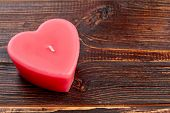 Natural Heart Shaped Red Candle. Wax Heart Shaped Candle On Brown Wooden Background And Copy Space.  poster