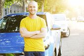 Portrait Of Smiling Young Man In Yellow T-shirt Leaning On His New Caribbean Blue Car. Handsome Fit poster