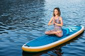 Young Woman Meditating On Paddle Board. Practice Yoga On Paddle Board, Woman Sitting On Paddle Board poster