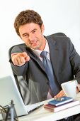 Smiling Modern Businessman Sitting At Office Desk And Pointing On You