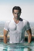 Fashion portrait of a gorgeous male model in soaked wet t-shirt standing in luxurious swimming pool
