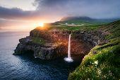 Incredible sunset view of Mulafossur waterfall in Gasadalur village, Vagar Island of the Faroe Islan poster
