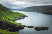 Dramatic view of green hills of Vagar island and Sorvagur town on background. Faroe islands, Denmark poster