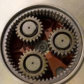 Three Metal Gears In A Large Gear Mechanism . Industrial Equipment. Close Up. poster