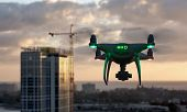Unmanned Aircraft System Quadcopter Drone In The Air Near City and Corporate Building. poster