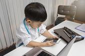 Little Boy In Medic Uniform Using A Cellphone On Desk. poster