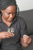 African American Woman Taking Pill And Holding Glass Of Water. African American Woman Has Runny Nose poster