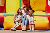 Mother And Her Daughters Sitting On Jumping Castle