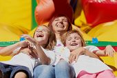 stock photo of bouncing  - Mom and her daughters laughing out loud laying on a bouncing castle in a bright summer day outdoors - JPG