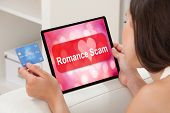Close-up Of A Woman Using Laptop With Romance Scam Application On Screen Sitting At Home poster