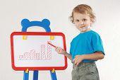 Weinig schattige lachende jongen trok een diagram van de groei op het whiteboard