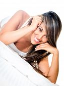Beautiful woman lying in bed and smiling - isolated over white