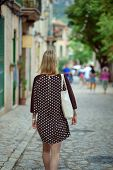 European Woman In Polka-dot Dress Is Travelling In The Beautiful City Center Of A European Town. Bac poster