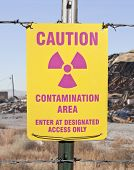 Caution radioactive contamination warning sign with barb wire fence.