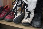Bunch Of Abandoned Boots With Torn Sole Placed On Wooden Shelf poster