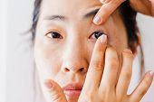 Beautiful Woman Putting Eye Lenses With Hands poster