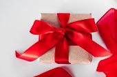 Gift Box With Craft Paper And Red Ribbon On A White Background. Beautiful Gift Box With Craft Paper  poster