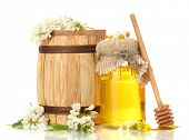 Sweet honey in barrel and jar with acacia flowers isolated on white
