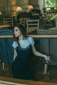 Beautiful Elegant Brunette Girl Wearing A Black Dress Is Relaxing In A Street Cafe. Advertising,fash poster