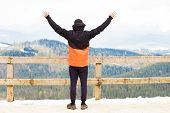 Man Stands On Edge Of Observation Deck. Grandiose Panorama On Top Of Mountains Covered Snow poster