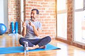 Middle age handsome sportman sitting on mat doing stretching yoga exercise at gym Pointing aside wor poster