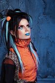 Rock Girl With Blue Lips And Punk Hairstyle Leaning Against Grunge Wall