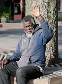 image of hobo  - Elderly African American homeless man waving while sitting outdoors - JPG