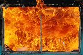 stock photo of infernos  - Window Screen Inferno the results of a fire in a old office building being burnt as for fire department training - JPG