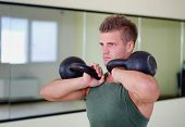 stock photo of kettlebell  - Attractive young athletic man exercising in gym working out using kettlebells - JPG