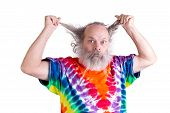 stock photo of shaving  - Time for a haircut if your hair driving you nuts perhaps time to shave your beard too senior with his tie dye shirt looking for haircut - JPG