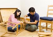 Asian couple assembling chair