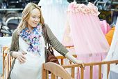 Young pregnant woman choosing cot or bassinet for newborn baby at infant shop