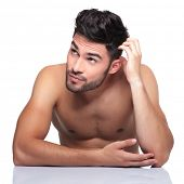 young naked beauty man scratching his head and looking up to his side on white background