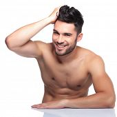young laughing man is posing for the camera while passing his hand through his hair