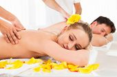 image of deep-tissue  - Attractive couple lying side by side in a spa enjoying the luxury of a deep tissue back massage together - JPG