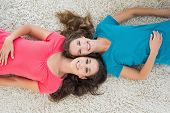High angle portrait of two young female friends lying on rug in the living room at home