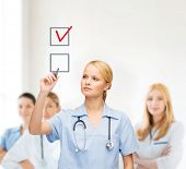 healthcare, medical and technology - young doctor or nurse with marker drawning red checkmark into c