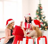 shopping, sale, gifts, christmas, x-mas concept - smiling women in santa helper hats with shopping b