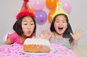 Close-up of two young girls blowing cake at a birthday party