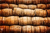 stock photo of scotch  - Stacked pile of old whisky and wine wooden barrels in vintage style