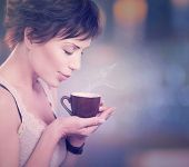 Beautiful Girl Drinking Tea or Coffee. Beauty Woman with Cup of Hot Beverage. Enjoying Coffee. Paste