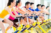 picture of exercise bike  - Chinese Asian sport group of men and women in fitness club or gym exercising on bikes - JPG