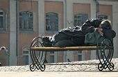stock photo of hackney  - the homeless sleeps on a bench in beams of the morning sun - JPG