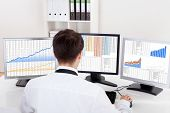stock photo of ascending  - Over the shoulder view of the computer screens of a stock broker trading in a bull market showing ascending graphs
